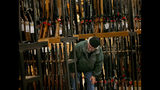 FILE - In this Nov. 29, 2019, file photo, a man looks at the shotgun section of Cabela's while shopping on Black Friday in Hazelwood, Mo. The number of background checks conducted by federal authorities is on pace to break a record by the end of this year. (Christian Gooden/St. Louis Post-Dispatch via AP)