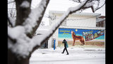A pedestrian walk through the snow past a mural, Tuesday, Dec. 3, 2019, in Providence, RI. (AP Photo/David Goldman)